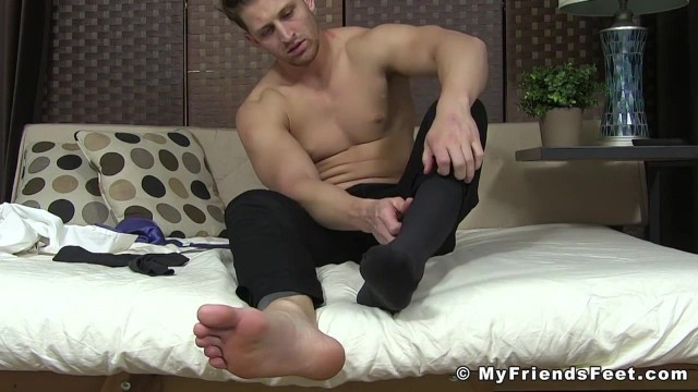 Striking stud in suit relaxes while playing with his feet